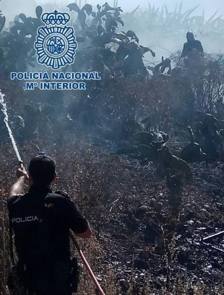 Un miembro de la Policía Nacional en la extinción del incendio (POLICÍA NACIONAL)